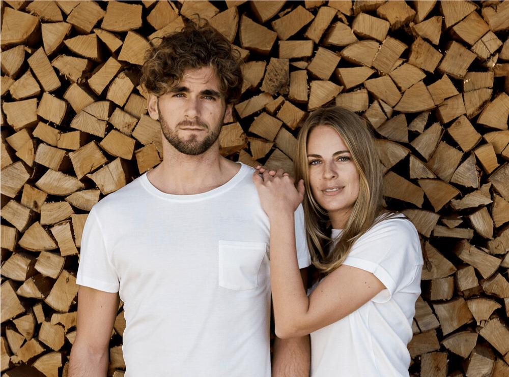 Das Bild zeigt zwei Models, einen Mann und eine Frau, die jeweils das MUNTAGNARD T-Shirt in weiß tragen, das erste plastikfreie T-Shirt vor einer Holzwand