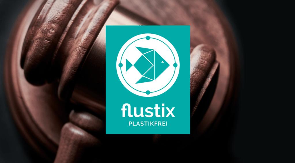 Logo des Flustix-Plastikfrei-Siegel, Hintergrund bildet ein Gerichts Hammer ab, Eigendeklaration Plastikfrei