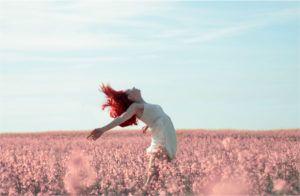 Frau posiert in einem Feld mit Blumen - suggeriert Freiheit, plastikfreie Periode
