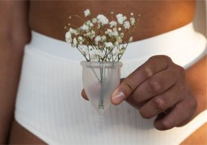 Frau hält eine Menstruationstasse in der Hand