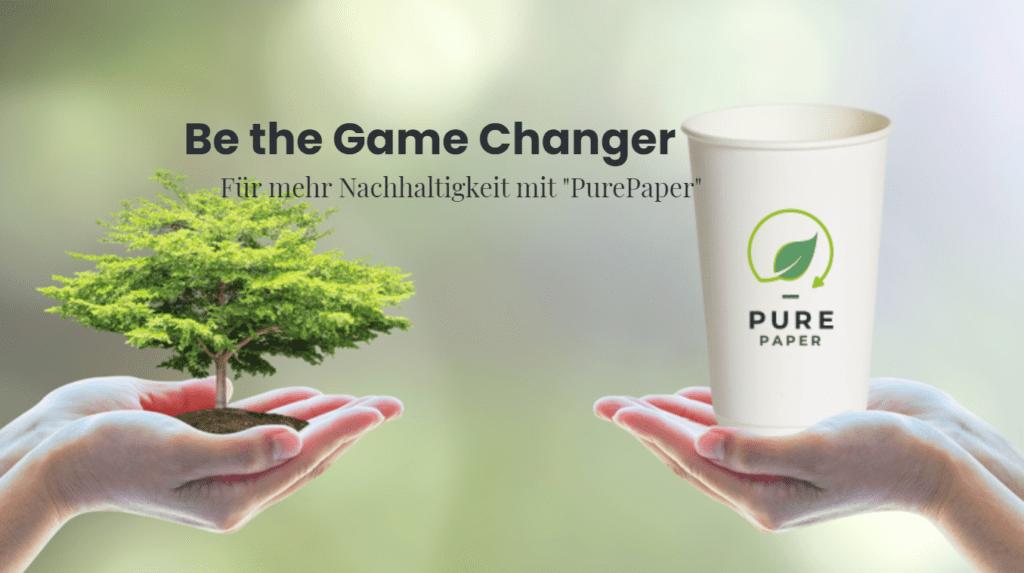 Headline des Bildes: Be the Game changer. Die Hand links im Bild hält symbolisch einen Baum, auf der anderen Seite ist eine Hand mit dem Pure Paper Cup, den ersten plastikfreien Pappbecher zu sehen.