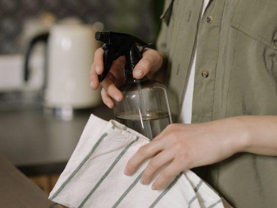 Frau hält Reinigungsmittel als Sprühfalsche in der Hand; Reinigungstabs als plastikfreie Alternative
