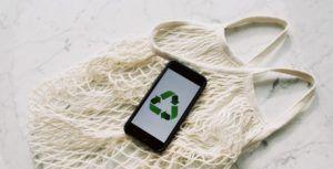 Auf einem Smartphone ist das Zeichen für Recycling abgebildet, das Smartphone liegt auf einer Tragetasche